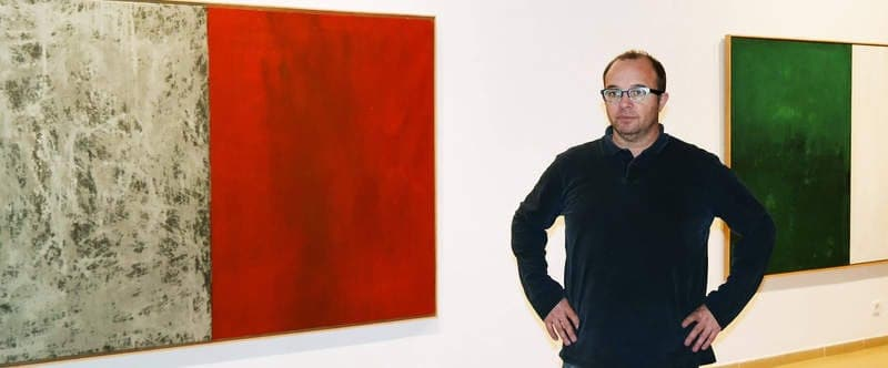 El artista coyantino posa ante dos obras de la exposición 'Intuición' que exhibe en el Instituto Leonés de Cultura. © Fotografía: Cuevas.