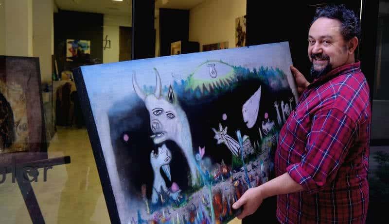 El artista leonés José de León sostiene una obra en la que hace un guiño al Guernica de Picasso. Foto: CUEVAS.